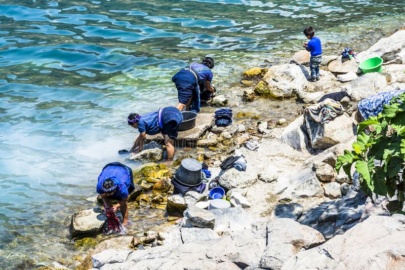 As senhoras nativas do Maya lavam a lavanderia na beira do lago, San Antonio Palopo, lago Atitlan, Guatemala fotos de stock