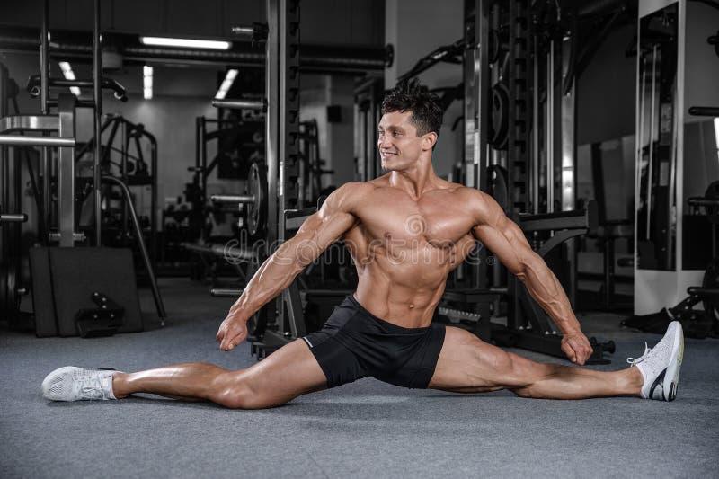 As separações esticam o homem que estica os pés na aptidão considerável do gym fotografia de stock royalty free