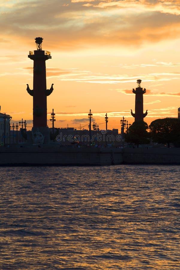 As silhuetas das colunas Rostral no por do sol St Petersburg foto de stock