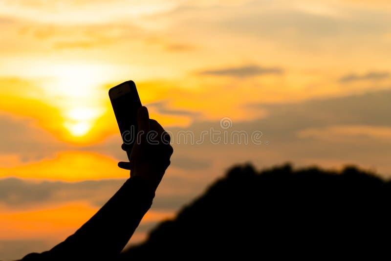 As silhuetas das jovens mulheres que sentam-se durante o por do sol e tomam um selfie com smartphone Moderno que tem o divertimen fotos de stock royalty free