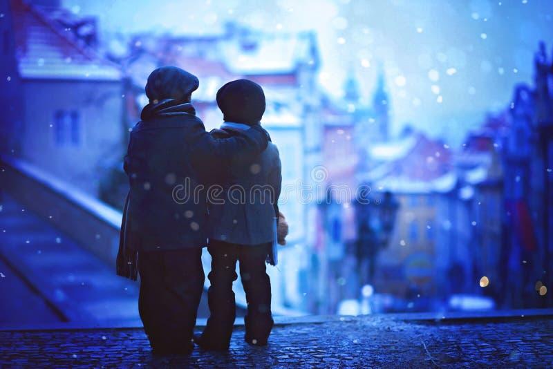 As silhuetas de duas crianças, estando no escadas, vista de Praga sejam imagem de stock royalty free