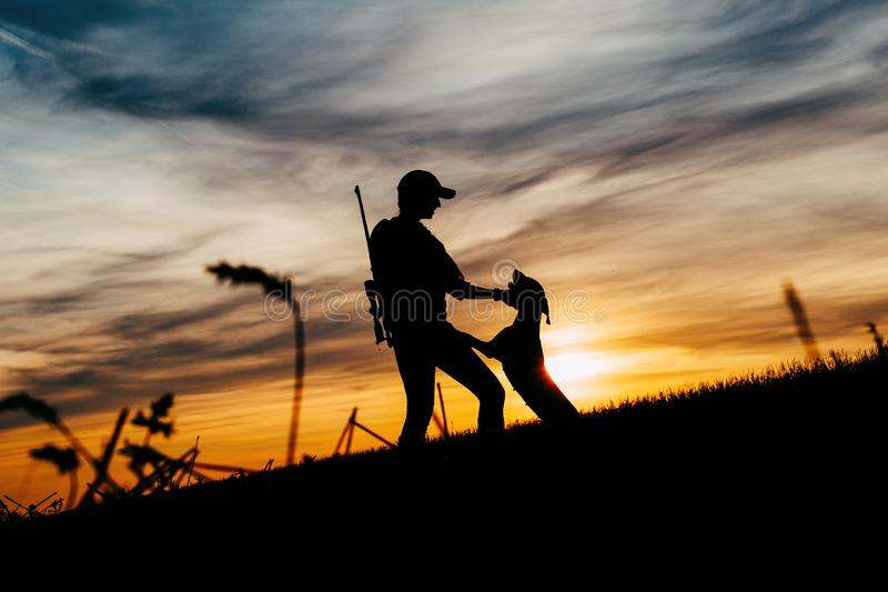 As silhuetas de uma menina com um rifle e seu cão, atrás deles são um por do sol bonito fotografia de stock royalty free