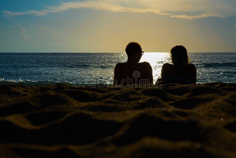 As silhuetas de uns pares, de um homem e de uma mulher estão sentando-se em um Sandy Beach e estão olhando-se o por do sol no mar imagens de stock