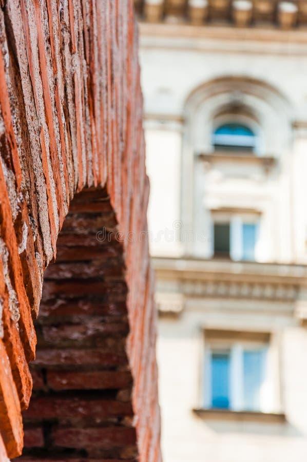 As sobras da civilização do império romano Close-up romano do arco do tijolo vermelho com a fachada clássica da construção reside fotos de stock