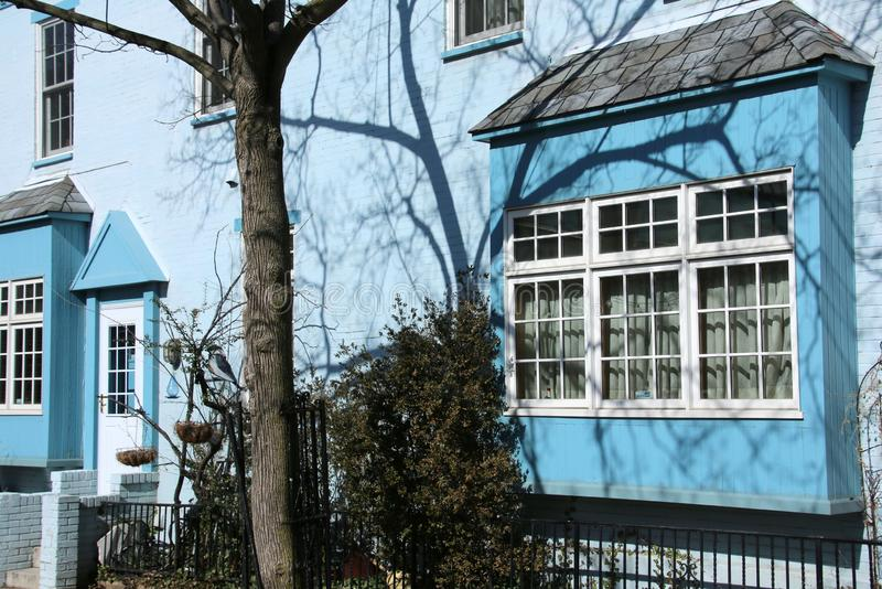 As sombras da tarde destacam esta casa azul imagem de stock royalty free