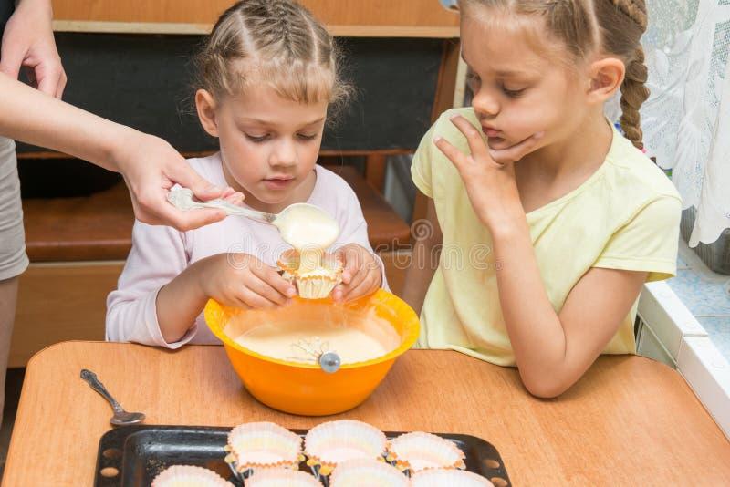 As subsidiárias das ajudas da mamã derramam a massa em moldes para bolos de cozimento fotos de stock royalty free