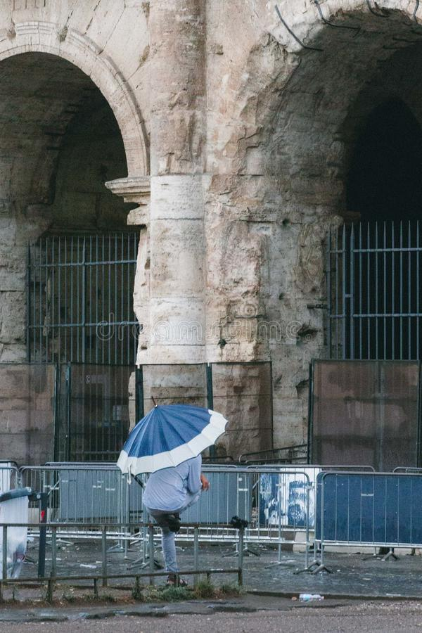 Rome Rain Afternoon, Lazio, Italy. As summer transitions to autumn, Rome often sees a newfound appreciation for rain. Umbrellas are widely available for passing stock photo