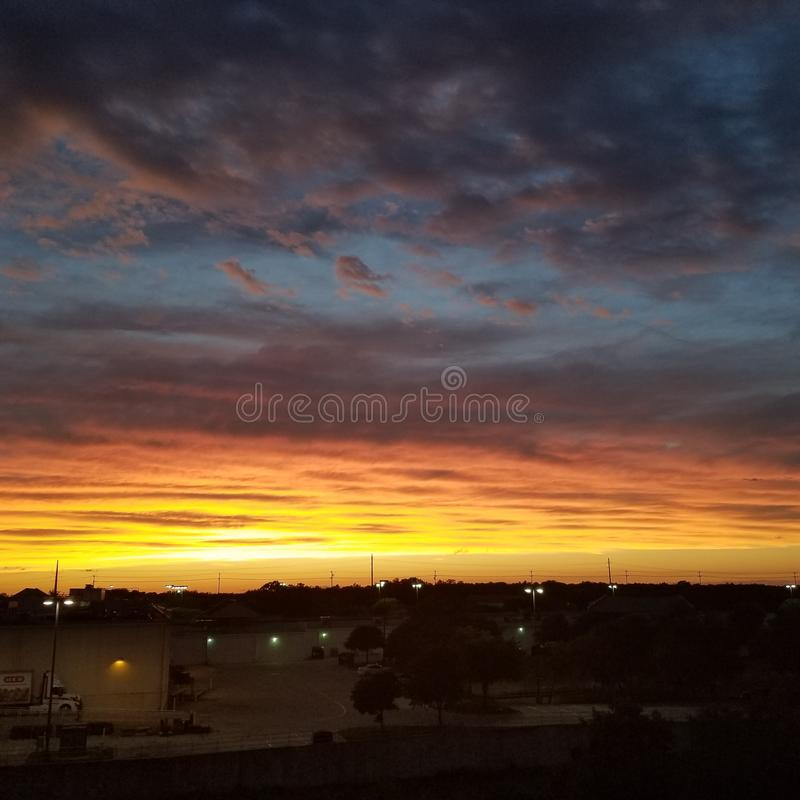 Colorful Sunset. As the sun disappears over the horizon, the clouds reflect and refract beautiful colors from orange and red to a dark blue stock photography