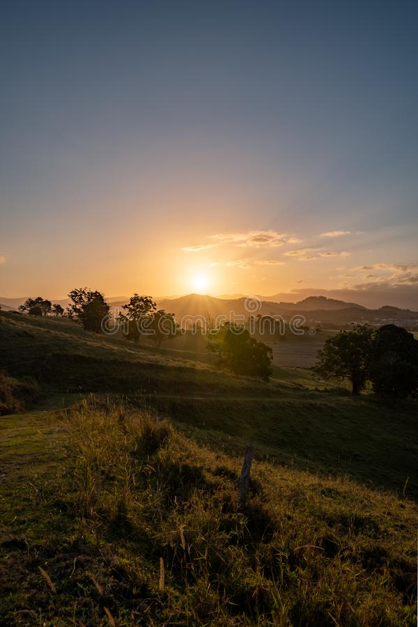 Dramatic sunset over Murwillumbah. As the sun sets it casts beautiful colours and shadows across the farm fields and landscape of Murwillumbah, NSW, Australia royalty free stock image