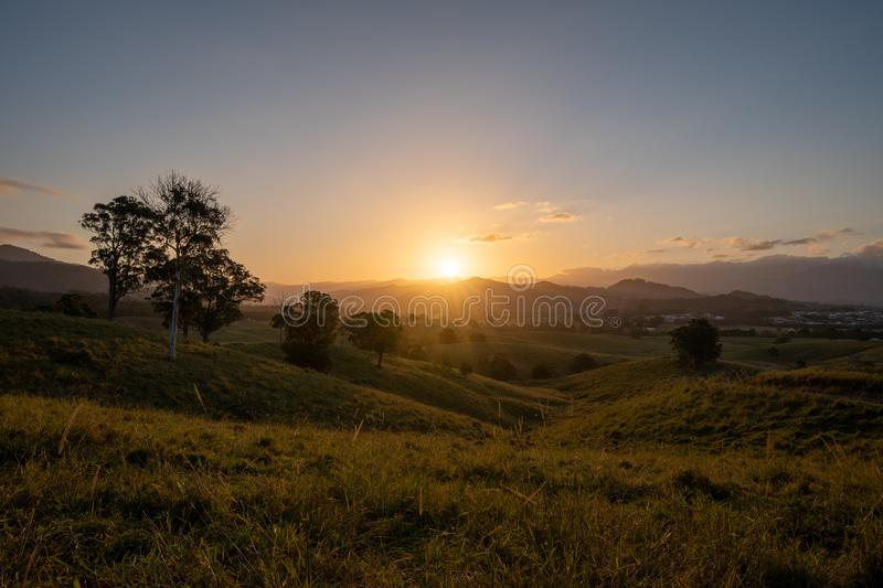 Dramatic sunset over Murwillumbah. As the sun sets it casts beautiful colours and shadows across the farm fields and landscape of Murwillumbah, NSW, Australia royalty free stock photos