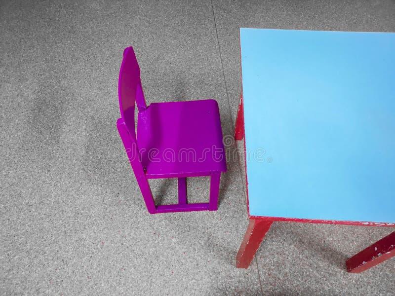 As tabelas e as cadeiras pequenas perto do quadro-negro na parede nas crian?as batem foto de stock royalty free