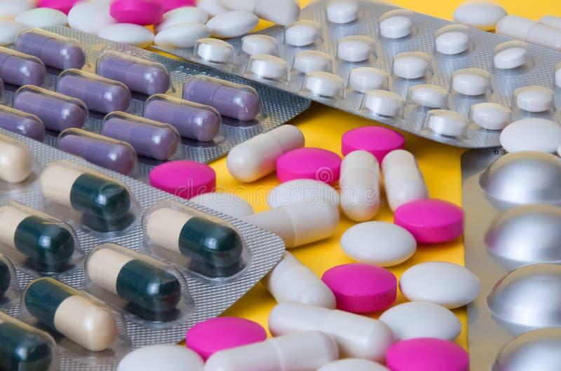 As tabuletas e as bolhas brancas e cor-de-rosa com comprimidos coloridos são dispersadas Vista lateral imagem de stock