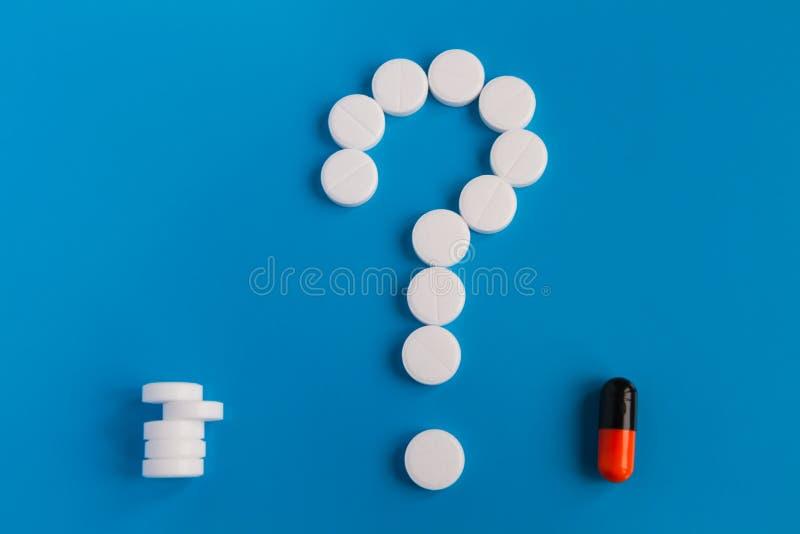 As tabuletas são meds brancos em um fundo azul Um símbolo de um ponto de interrogação Escolha entre comprimidos múltiplos e compr imagens de stock