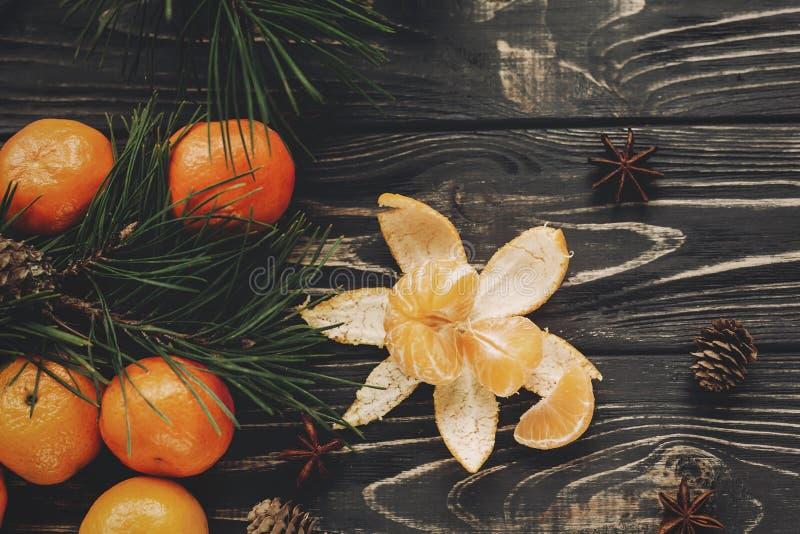 As tangerinas com abeto verde ramificam com cones e anis no rusti imagem de stock