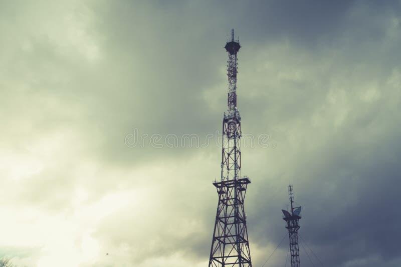 As telecomunicações de rádio elevam-se, torres do telefone celular e tubulação de aço velha em nuvens de tempestade paisagem dram imagens de stock royalty free