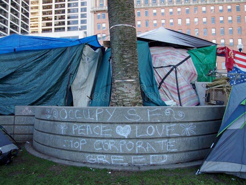 As tendas cercam muro com a escrita do Occupy SF, Peace, Love, Stop Corporate Greed in Chalk imagem de stock