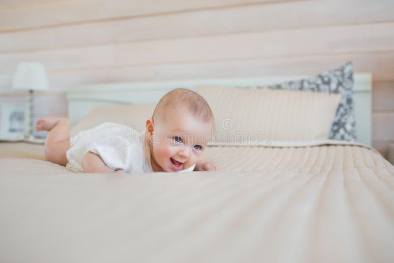 As tentativas consideravelmente pequenas do bebê de levantam-se em uma cama fotos de stock royalty free
