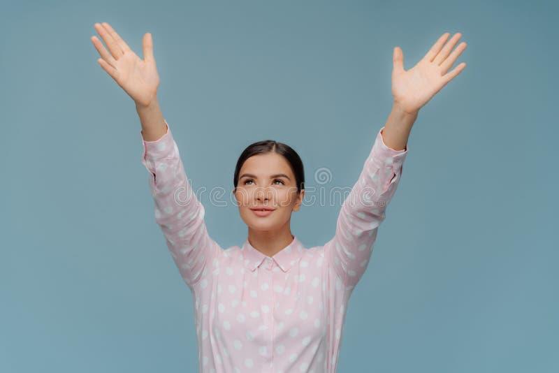 As tentativas fêmeas da morena bonita alegre para travar algo que cai do céu, mãos dos estiramentos focalizadas para cima, mostra fotos de stock