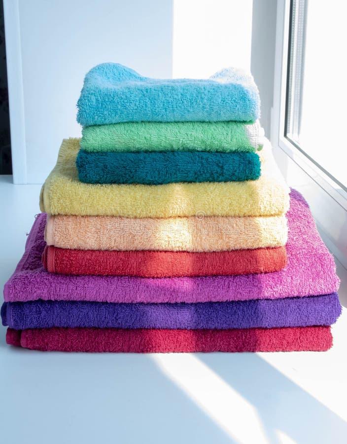 As toalhas de banho coloridas encontram-se na janela imagem de stock