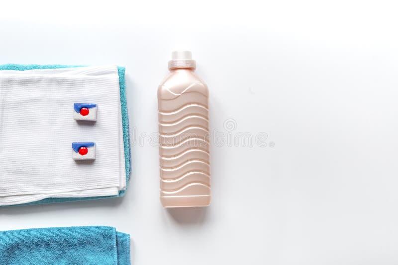 As toalhas empilham com as garrafas detergentes e plásticas no modelo da opinião superior da lavanderia foto de stock
