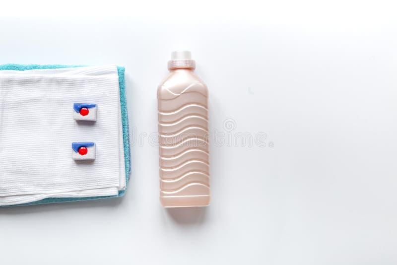 As toalhas empilham com as garrafas detergentes e plásticas no modelo da opinião superior da lavanderia fotografia de stock