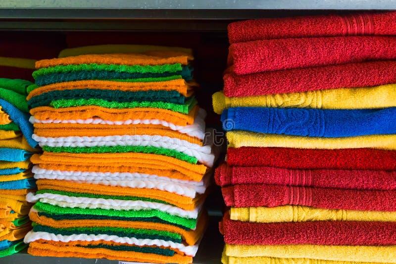 As toalhas frescas do hotel dobraram-se e empilharam-se em uma prateleira fotos de stock