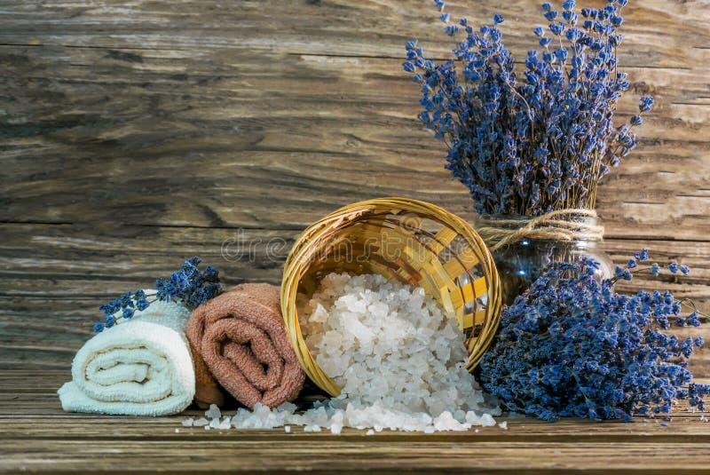 As toalhas, sal derramaram uma cesta de vime e dois ramalhetes da alfazema, uma de que está em um vaso de vidro Fundo de madeira fotos de stock royalty free