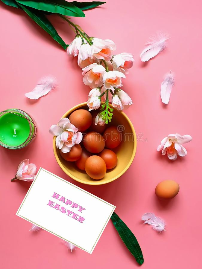 As toranjas vermelhas dos ovos da p?scoa felizes picam a placa amarela da vela verde branca do aroma das flores da ma?? no fundo  foto de stock