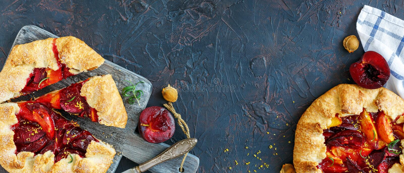 As tortas do verão com as ameixas vermelhas e amarelas no serviço embarcam fotografia de stock