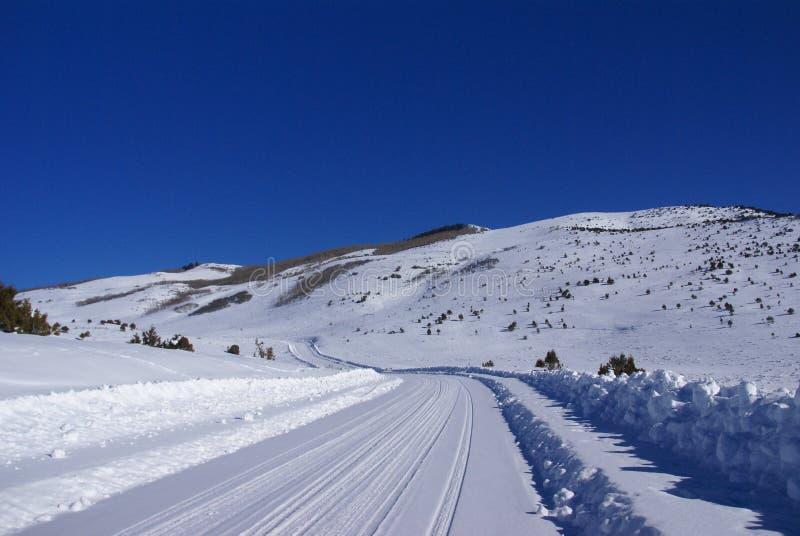 As trilhas na neve cobriram a estrada na montanha imagem de stock royalty free