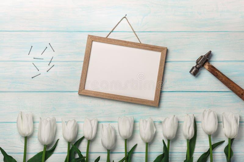 As tulipas brancas, riscam pregos da placa, do martelo e do metal em placas azuis Dia do `s da matriz fotografia de stock royalty free