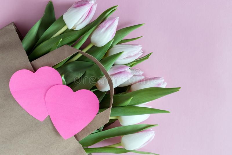 As tulipas cor-de-rosa frescas florescem no saco de papel com coração de papel imagens de stock royalty free