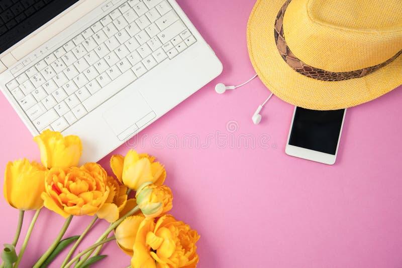 As tulipas, o portátil e o smartphone amarelos em um fundo lilás saltam, opinião superior colocada plano Copyspace do conceito do fotos de stock royalty free
