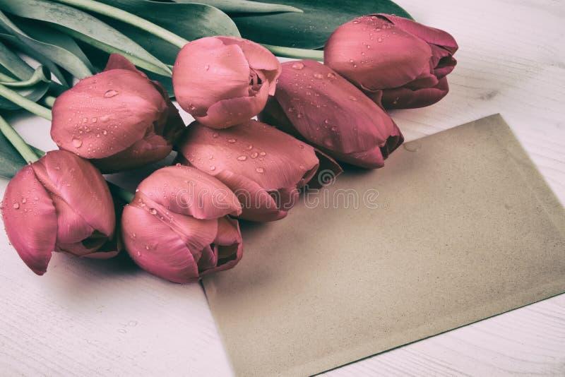 As tulipas vermelhas com vintage de papel da folha denominam ainda a vida retro imagens de stock royalty free