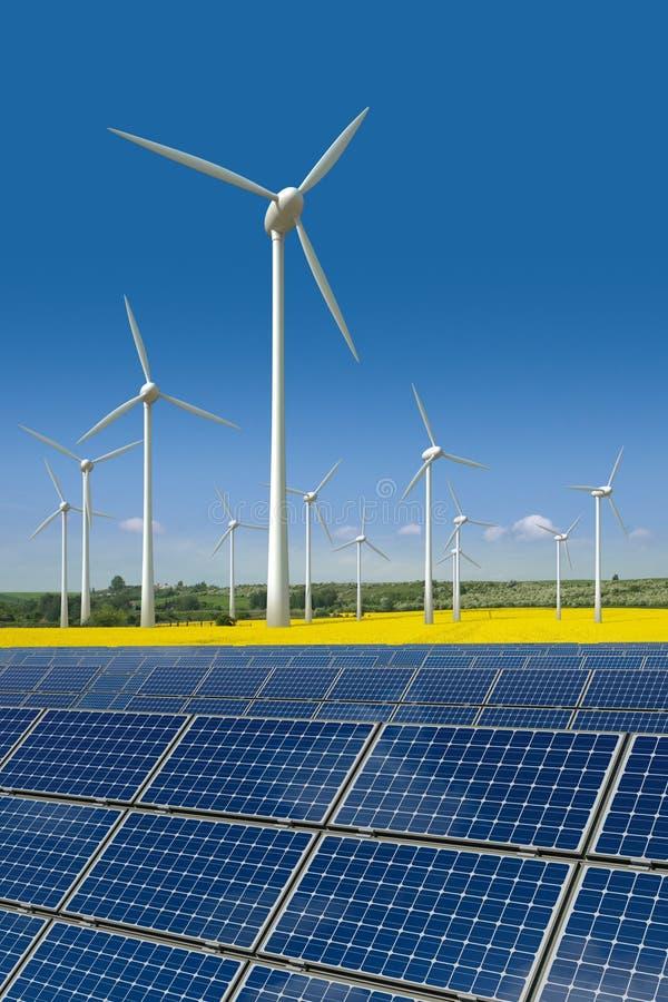 As turbinas de vento e os painéis solares em um rapeseed colocam foto de stock royalty free