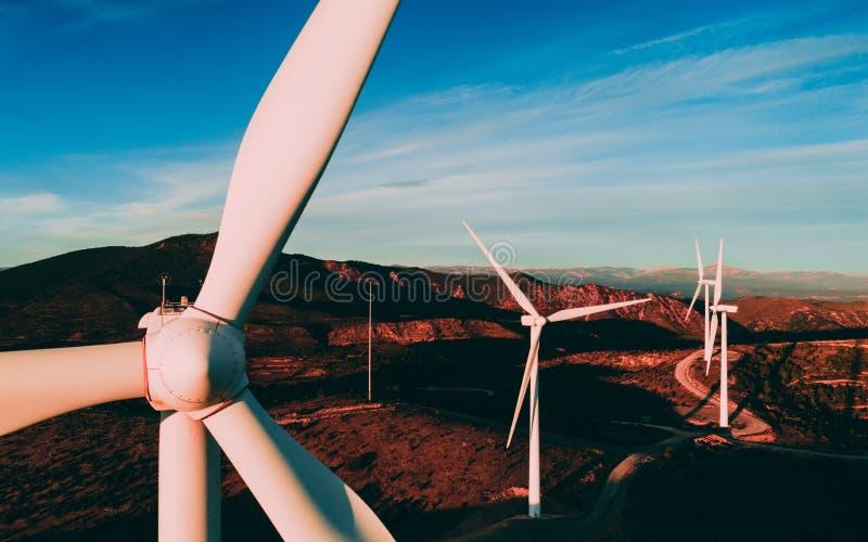 As turbinas eólicas brancas ou os moinhos de vento modernos nas montanhas ajardinam imagens de stock