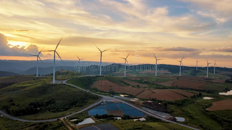 As turbinas eólicas da paisagem do por do sol cultivam a energia verde limpa para elegem foto de stock