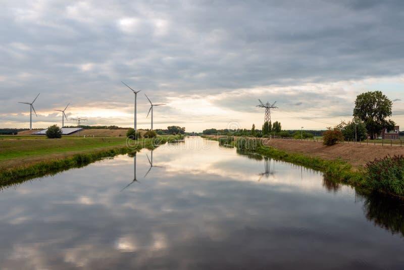 As turbinas eólicas e os pilões de alta tensão refletiram na água imagens de stock