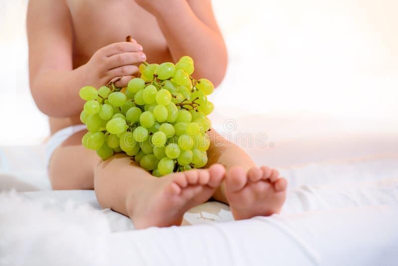 ? as uvas dos pés do ` s do hild em um fundo branco comem foto de stock