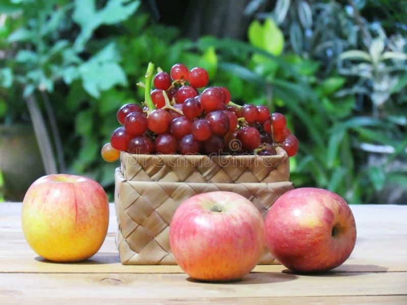 As uvas estão na caixa e nas maçãs do weave no assoalho de madeira com gree imagens de stock