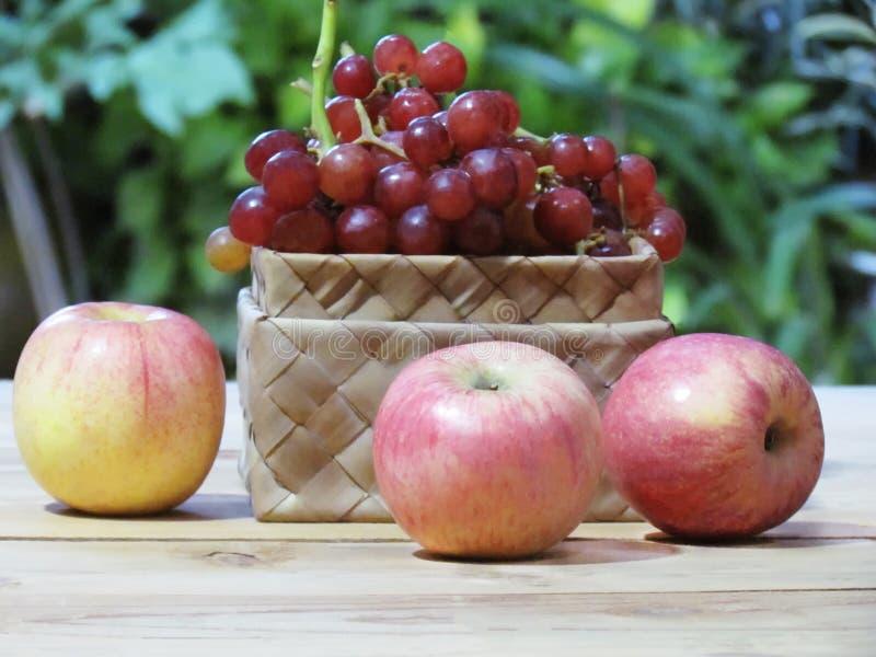 As uvas estão na caixa e nas maçãs do weave no assoalho de madeira com gree fotos de stock royalty free