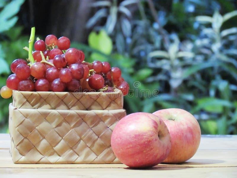 As uvas estão na caixa e nas maçãs do weave no assoalho de madeira com gree foto de stock