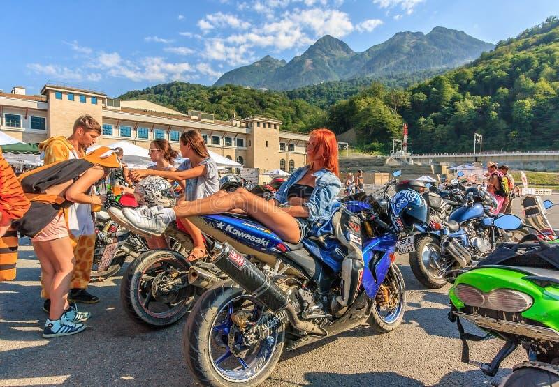 As várias motocicletas estacionaram fora no fundo do verão do pico de montanha e aprontam-se para a mostra do velomotor Povos que fotos de stock