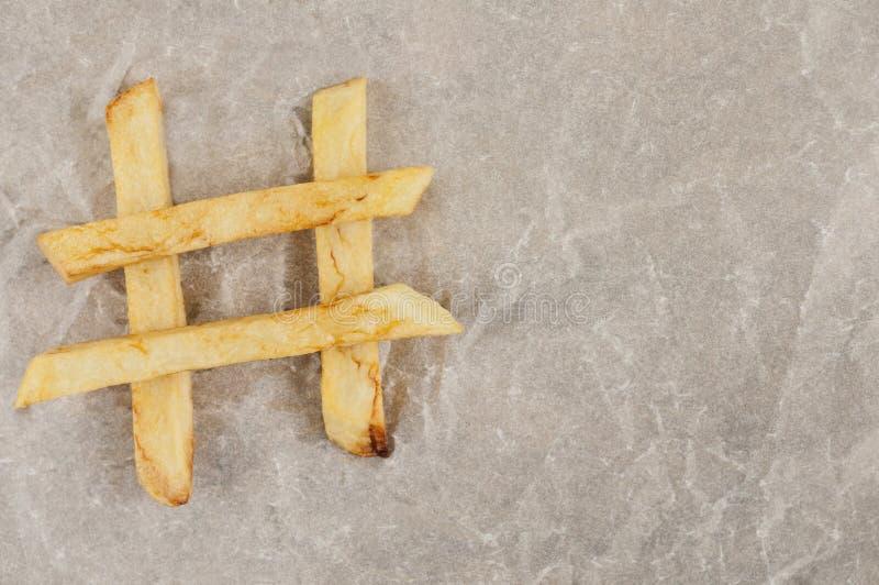 As varas das batatas fritas apresentadas no formulário do sinal do hashtag no cinza amarrotaram o papel Vista superior foto de stock