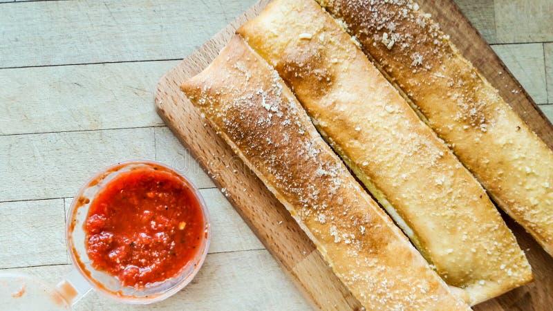 As varas de pão do alho com queijo parmesão e salsa mergulham o molho imagem de stock