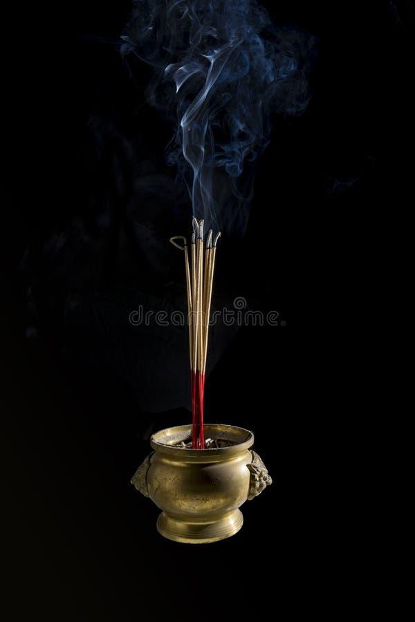 As varas do incenso estão queimando-se no potenciômetro do incenso no fundo preto O fumo durante o incenso cola o burning para fa fotos de stock royalty free