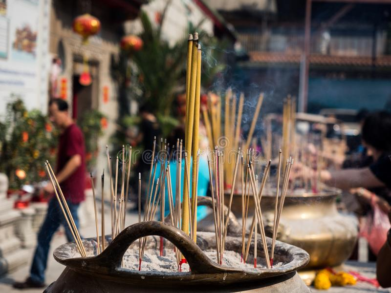 As varas do incenso na queimadura e no fumo do potenciômetro da vara de Joss usaram-se para pagar o respeito à Buda imagem de stock royalty free