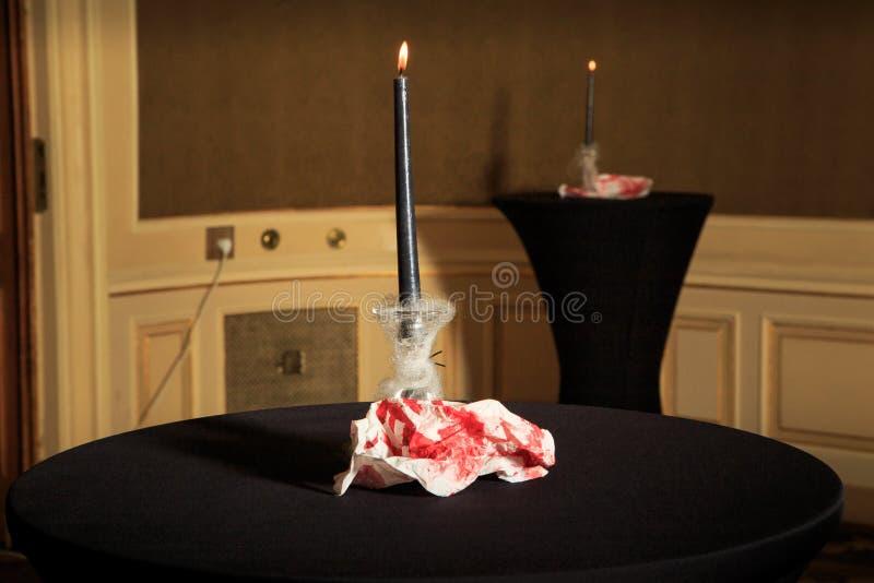 as velas e o vermelho pintaram guardanapo em tabelas pretas dos tecidos fotografia de stock