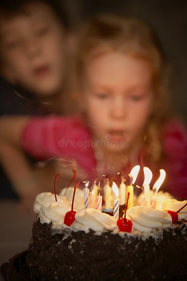 As velas festivas fundem para fora em um bolo de aniversário imagem de stock