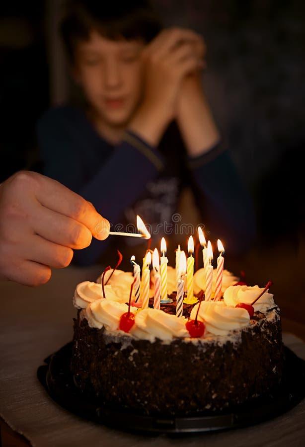 As velas festivas são iluminadas no bolo de aniversário imagens de stock